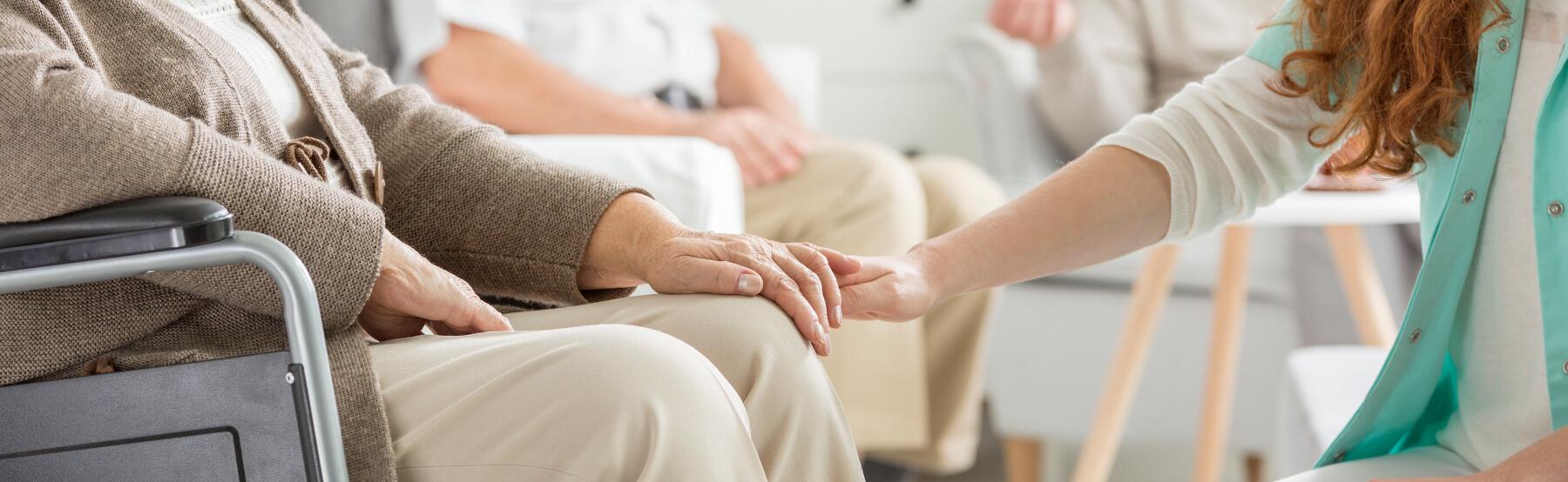 Sestra drží seniora za ruku doma.
